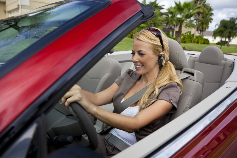 beautiful-young-woman-driving-convertible-car-talking-on-bluetooth-headset